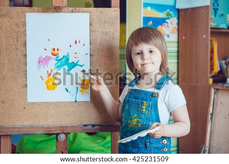 The girl draws a painting at the easel - stock photo