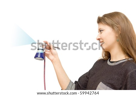 The girl draws in air brush, white a background - stock photo