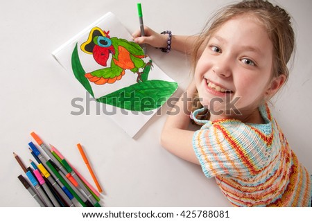 The girl draws lying on the floor, the girl paints a parrot - stock photo