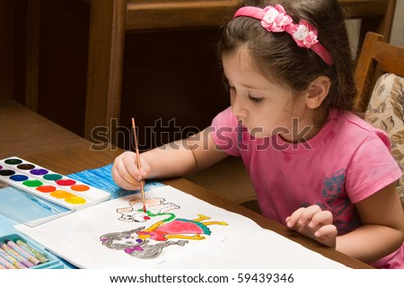 The girl draws water colour paints