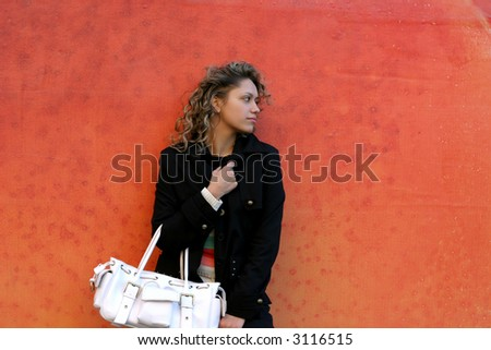 the girl dressed in black with white handbag on orange