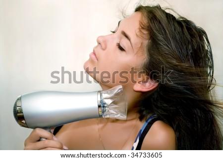 The girl dries hair the hair dryer - stock photo