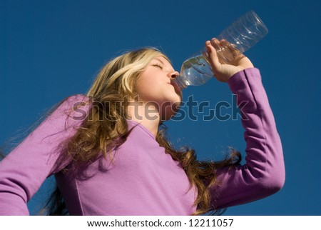 The girl drinks water from a bottle against the sky