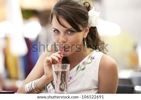 the girl drinks water from a glass through a straw. the nice European satisfies thirst in summer cafe - stock photo