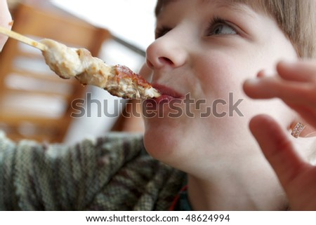 The girl eats a tasty meat on skewer - stock photo
