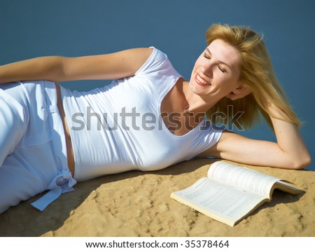 The girl has a rest with the book on a beach on coast of the river