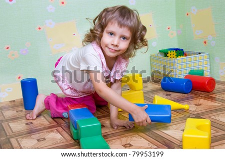 The girl has built a tower out of blocks, the interior - stock photo