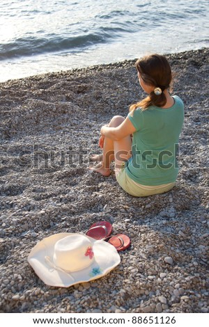 The girl, hat and flip-flops on the stones outdoors shooting - stock photo