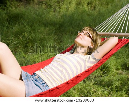 The girl having a rest in a hammock on a glade in wood - stock photo