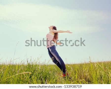 The girl, having stretched hands, enjoys a sunlight - stock photo