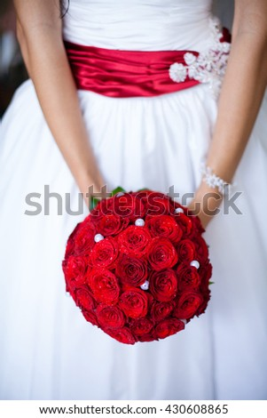The girl holds a bouquet of red roses in hand. Bride holds a wedding bouquet. Wedding dress.