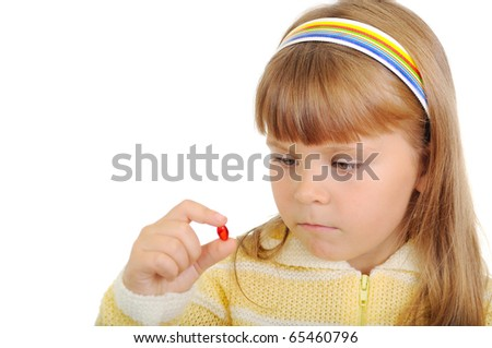 The girl holds a medicinal capsule in a hand isolated on white