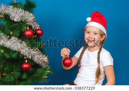 The girl holds a New Year's toy in hand and smiles. Christmas. New year.