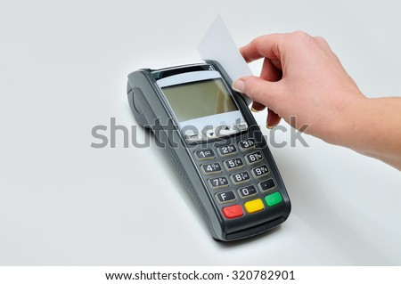 The girl holds in hand a credit card in front of the terminal on white background. A white credit card without image. Payment by a credit card in the terminal - stock photo