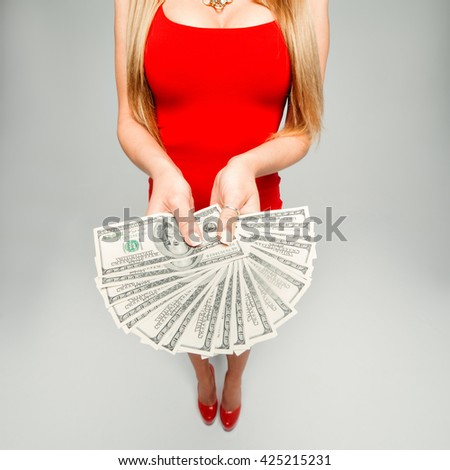 The girl holds in hands a lot of money. The woman in the red dress and red shoes with a fan of banknotes in his hands, his chest. - stock photo