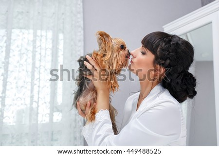 The girl holds in her arms and kisses her Yorkshire terrier. Home pet. Pedigree dog. Funny animals. - stock photo