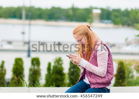 The girl holds phone in hand. Portrait of a girl