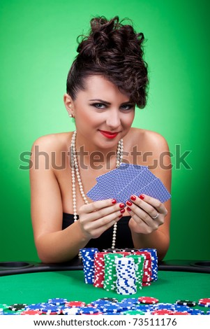 The girl in a black dress with five cards on a green background