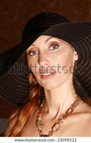 The girl in a black hat against a dark background
