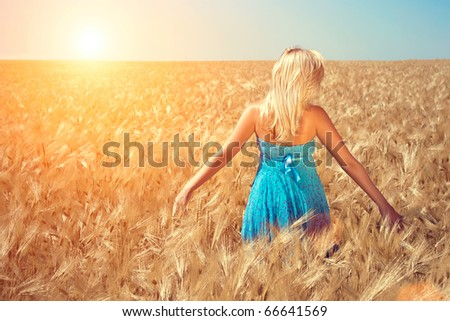 The girl in a blue dress runs on a wheaten field to the sun - stock photo