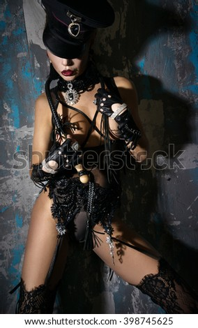 The girl in a cap and beautiful lingerie, standing near the wall with a whip