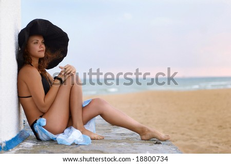 The girl in a hat sits - stock photo