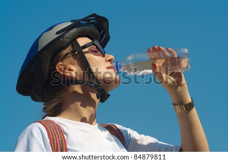 The girl in a helmet drinks water - stock photo