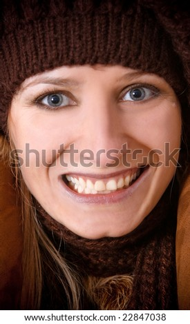 The Girl in a knitted cap smiles - stock photo