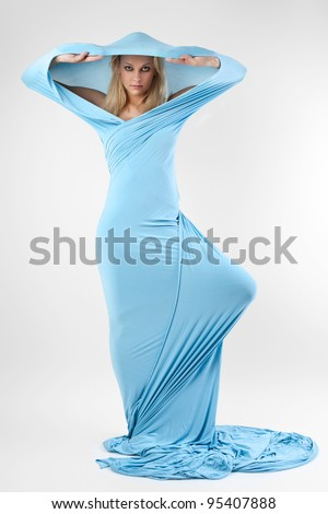 The girl in a long blue dress on grey background. - stock photo