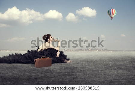 The girl in a luxurious dress with a suitcase dreaming of faraway countries sitting outdoors. - stock photo