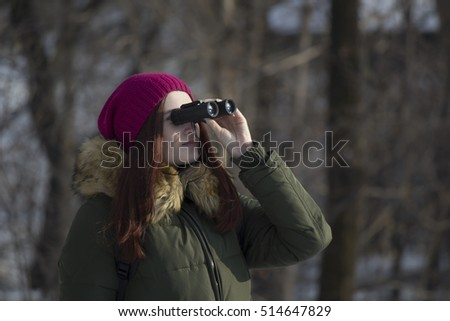 The girl in a pink cap with a backpack in the winter in a forest looking through binoculars