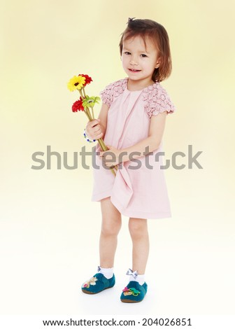 The girl in a pink dress with a bouquet of flowers.Happiness concept,happy childhood