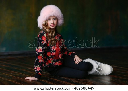 The girl in a pink fur hat, fur boots, bright blouse and sitting on the floor in the room. Fashion  - stock photo
