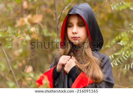 The girl in a red and black cape in the forest - stock photo