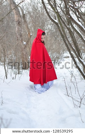 The girl in a red raincoat goes on a winter forest and looks back - stock photo