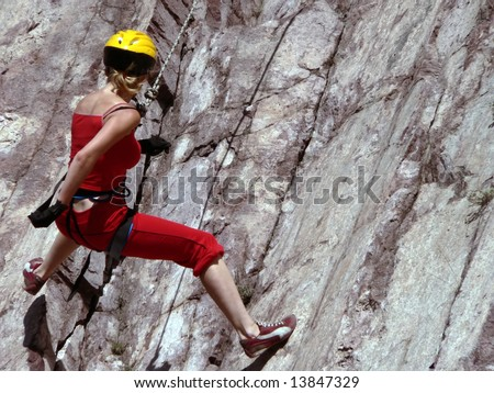 The girl in a red suit is engaged in rocky mountaneering - stock photo