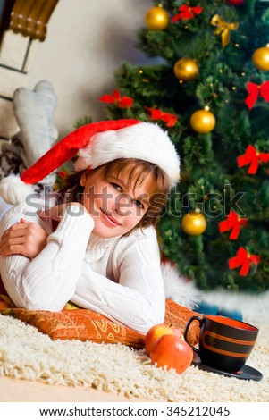 The girl  in a Santa hat near the Christmas tree in a house interior - stock photo