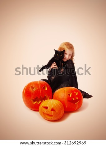 The girl in a suit of a witch with black cat - stock photo