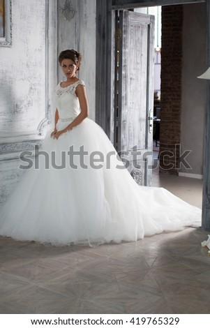 The girl in a wedding dress. Bride near the window. Fashion photo shoot wedding dress. Wedding dress in Paris. Bride in a luxury apartment in a wedding dress.