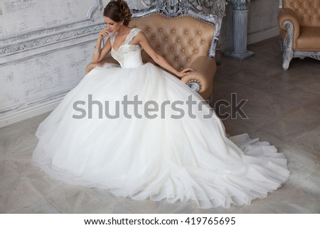 The girl in a wedding dress. Bride near the window. Fashion photo shoot wedding dress. Wedding dress in Paris. Bride in a luxury apartment in a wedding dress. - stock photo