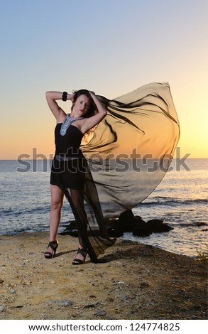 The girl in an evening dress on the seashore. Decline. Wind