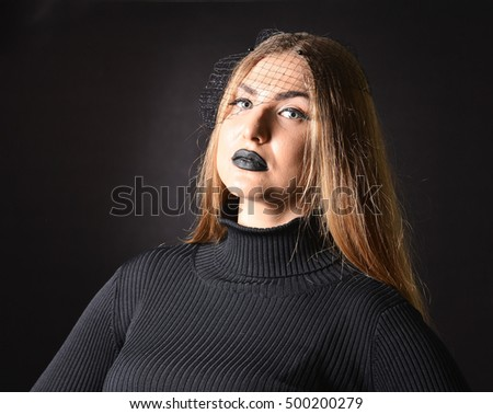 The girl in black clothes and black make-up in studio