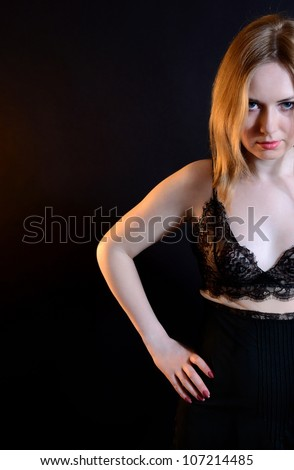 The girl in black clothes on a black background. Looks frowningly - stock photo