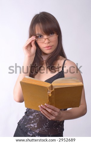 The girl in glasses reads the book on a grey background