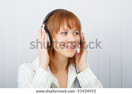 The girl in headphones listens to music with pleasure - stock photo