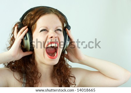 The girl in headphones shouts on a white background