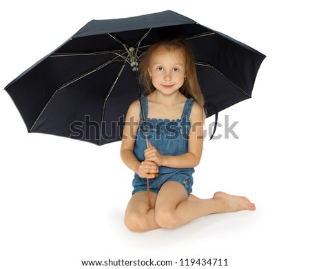 the girl in jeans shorts sits under an umbrella