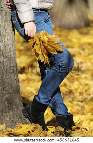 The girl in jeans standing near a tree with a bouquet of autumn leaves.
