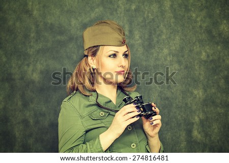 The girl in military clothes, in his cap, with binoculars. Victory Day on May 9. - stock photo