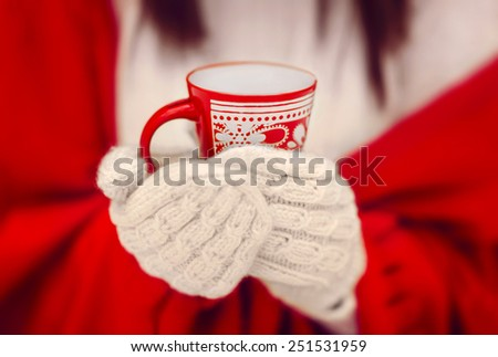 the girl in mittens holds a red cup in hand - stock photo